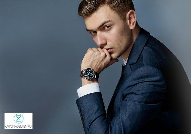 Hombre de perfil con traje mostrando su reloj