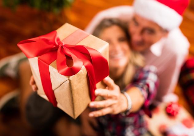 Pareja sosteniendo regalo de navidad