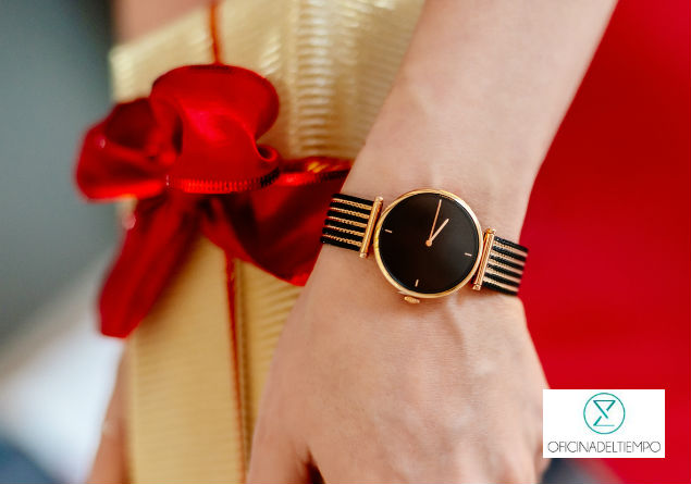 Persona con reloj sosteniendo regalo de navidad