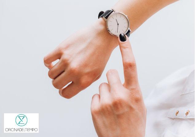 Mujer señalando su reloj de pulsera