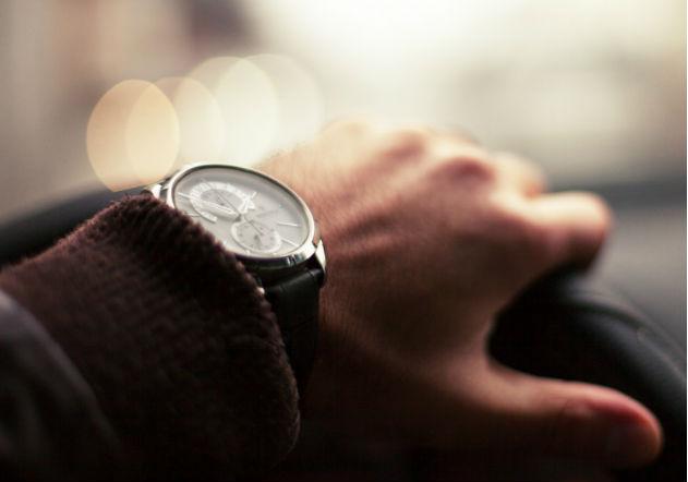 Mano sosteniendo timón de carro con reloj de lujo